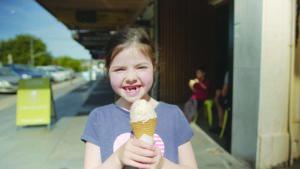 Little girl smiling while holding an ice-cream cone